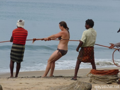 Lady Christ among the fisher folk: A white woman helping the fishermen to pull the loop-net from the sea at Black Beach, Varkala.