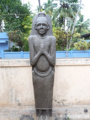 A granite idol recovered from a pond at the birth place of poet Kumaran Asan at Kayikara.  It is seen as Buddha by the local people.  Can be identified as a Siddha idol belonging to the late Vajrayana or Tantric Buddhist stage in Kerala history, the transitional period from Buddhism to Brahmanism in Kerala history.  Siddha is associated with Vajrayana while Arhat is associated with early Teravada or Hinayana and Boddhisatva is associated with Mahayana.  C V Kunhiraman has observed that Ezhava people traditionally worshiped the Chithan and Arathan.  Chithan is Sidhan and Arathan is Arhatan.  Boddhisatva has become Chathan.  It is also associated with Sastha another synonym for the buddha.  Idol now installed at Asan Memorial, Kayikara.