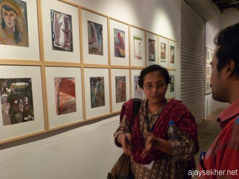 Artist Kabitha Mukherjee explaining about the gouache technique in K Prabhakaran's work exhibited with wonderful curatorial intervention at Aspinwall.
