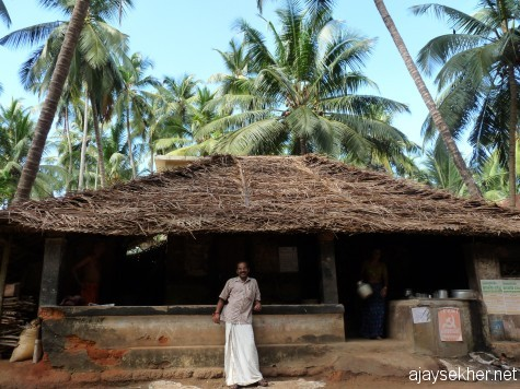 A humble coconut leaf thatched tea shop in Ezhava Thuruthy.  Mr Premdas Ponnani a local poet and artist before the humane hut amidst astonishing coconut groves by the Perar.
