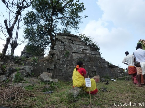 The remaining outer wall of Mangaladevi Kottam that was finely built.  A woman from Tamil Nadu sits a while after the 2 hour long queue to get in. 25 apl 2013.