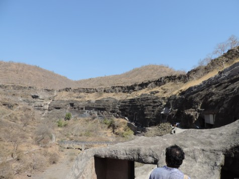 Ajanta caves from eastern entrance on the morning of Buddha Purnima, 25 May 2013.  Anirudh stepping on to the gateway.  River Waghora has dried up beneath in the late summer.