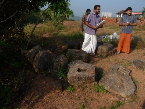 Relics and ruins on Ponnamkod hill the site of Trikaipata shrine.  Temple committee members among the granite pedestals and bases.