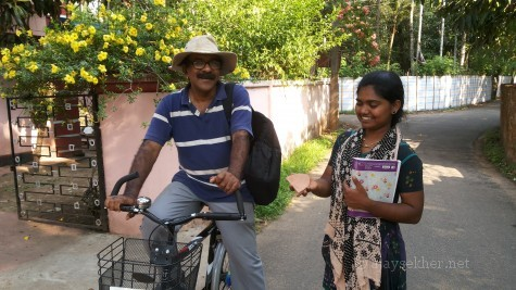 Prof P J Cherian on a cycle that is part of the green archeology of Pattanam project and Ms Mikky the research assistant with a Pattanam ware at Pattanam, 19 Apl 2014.